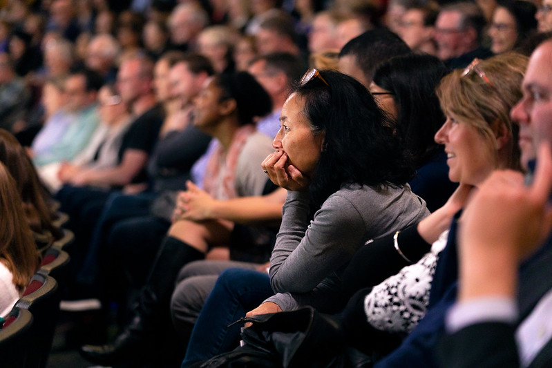 A woman in a full auditorium leans forward in her seat, rests her elbow on her knees