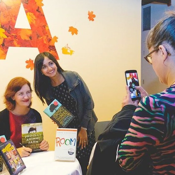 Someone taking a photo on their phone of Emma Donoghue signing a fan's book.