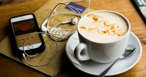 A cup of coffee with a phone playing music or a podcast.