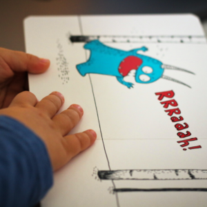 A drawing of a blue monster with a child's hands holding the page